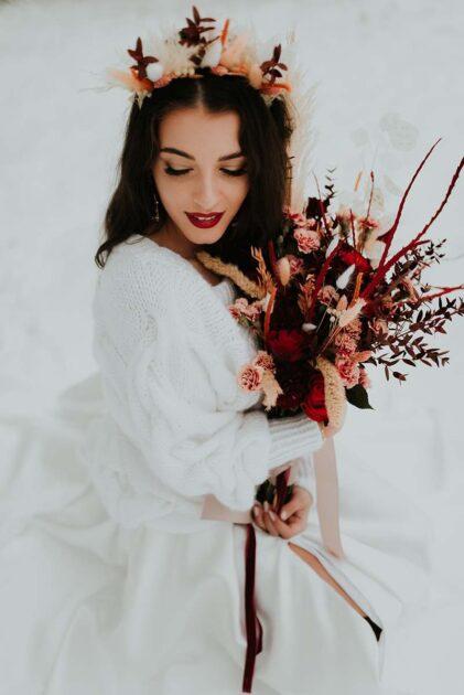 zimowa panna młoda w koronie z suszków z czerwonym bukietem