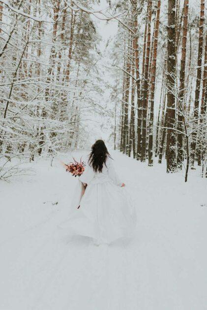 sesja ślubna w zimowym zaśnieżonym lesie i uciekająca panna młoda