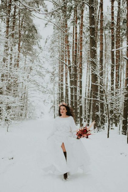 panna młoda z bukietem i koroną z suszek w zimowym lesie