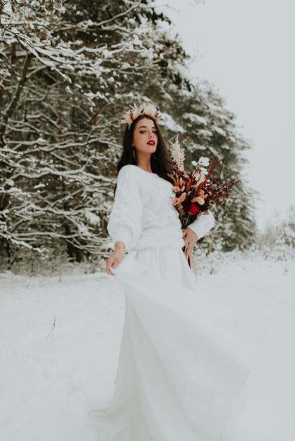 zimowa panna młoda z bukietem ślubnym i koroną z kwiatów