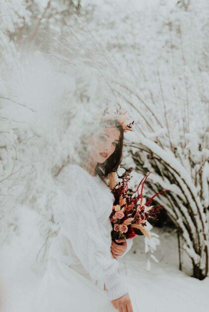 panna młoda w swetrze w zaśnieżonym lesie z bukietem ślubnym